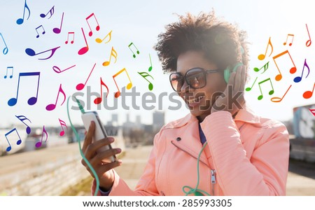 technology, lifestyle and people concept - smiling african american young woman or teenage girl with smartphone and headphones listening to music outdoors over colorful musical notes background - stock photo