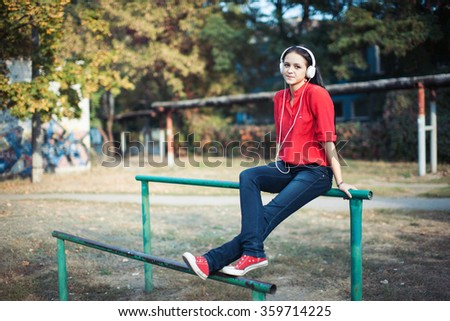 technology, lifestyle and people concept - smiling young woman or teenage girl with smartphone and headphones listening to music outdoors.