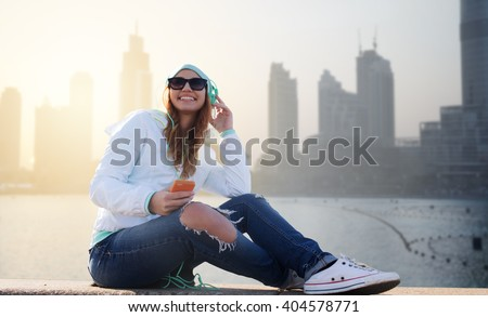 technology, lifestyle and people concept - smiling young woman or teenage girl with smartphone and headphones listening to music over dubai city street or waterfront background