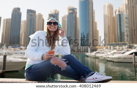 technology, lifestyle and people concept - smiling young woman or teenage girl with smartphone and headphones listening to music over dubai city street or waterfront with boats background - stock photo