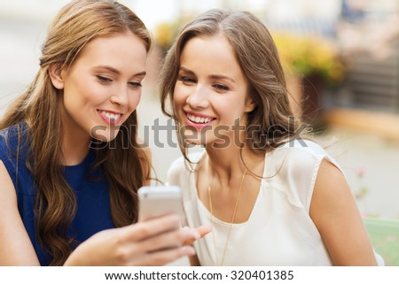 technology, lifestyle, friendship and people concept - happy young women or teenage girls with smartphone at outdoor cafe - stock photo