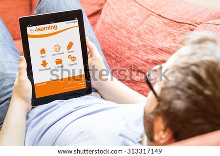 technology lifestyle learning concept: hipster man with online learning platform on a tablet at the sofa - stock photo