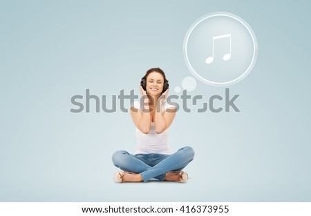 technology, music and happiness concept - smiling young woman or teen girl in headphones over blue background and musical note icon - stock photo