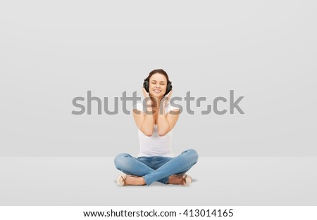 technology, music and happiness concept - smiling young woman or teen girl in headphones over gray background - stock photo