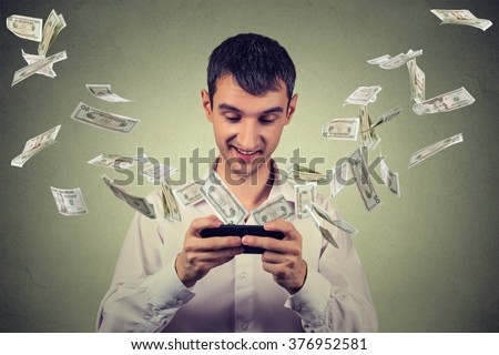 Technology online banking money transfer, e-commerce concept. Happy young man using smartphone with dollar bills flying away from screen isolated on gray wall office background. - stock photo
