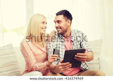technology, people, e-money and commerce concept - smiling happy couple with tablet pc computer and credit or bank card shopping online at home - stock photo