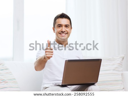 technology, people lifestyle and networking concept - happy man with laptop computer showing thumbs up at home - stock photo