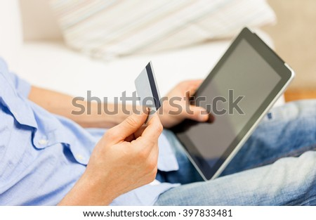 technology, people, online shopping, banking and lifestyle concept - close up of man with tablet pc computer and credit or bank card at home - stock photo