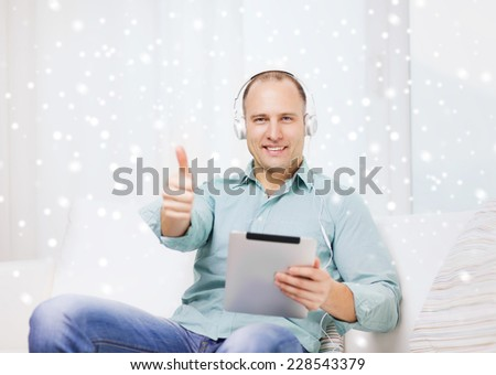 technology, people, winter, gesture and leisure concept - smiling man in headphones with tablet pc sitting on couch and showing thumbs up at home - stock photo