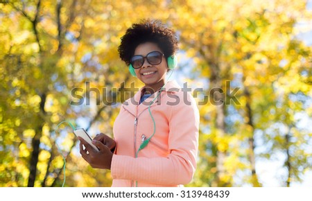 technology, season and people concept - smiling african american young woman or teenage girl with smartphone and headphones listening to music over autumn park background - stock photo