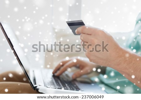 technology, shopping, banking, home and people concept - close up of man with laptop computer and credit card at home - stock photo
