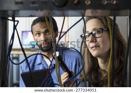 Technology team working together to repair and restore wire connection - stock photo