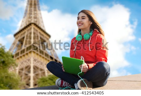 technology, travel, tourism, music and people concept - smiling young woman or teenage girl with tablet pc computer and headphones over paris eiffel tower background - stock photo