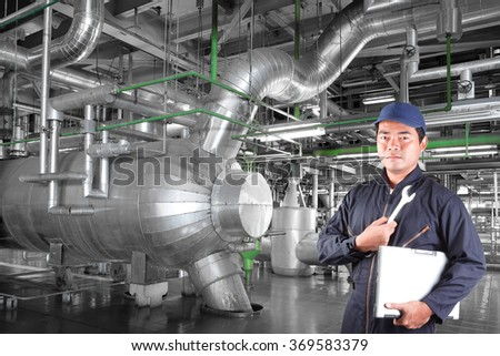 Tecnician holding computer and wrench for repair equipment and pipeline in a modern thermal power plant industrial