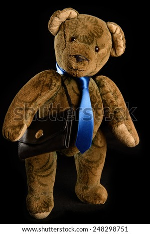 Teddy as a businessman with a blue tie and black briefcase. Studio shot, isolated against a black background shown - stock photo