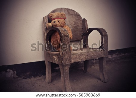 Teddy Bear alone on wooden chair