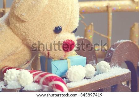 Teddy bear and Christmas present on a sleigh. Selective focus - stock photo