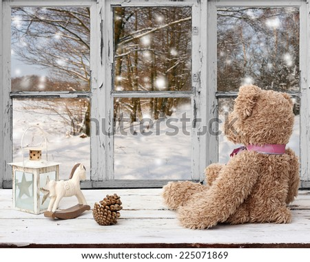 teddy bear and rocking horse looking at snowy day - stock photo