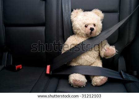 Teddy Bear buckled with safety belt in a car - stock photo