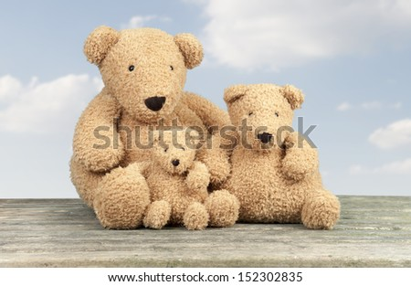 Teddy bear family, sky with clouds background - stock photo
