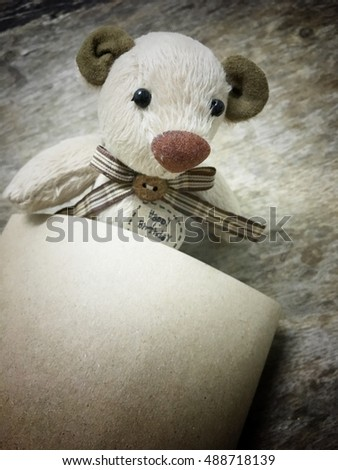Teddy bear for a birthday gift on wooden background. Handmade doll and vintage style birthday gift.