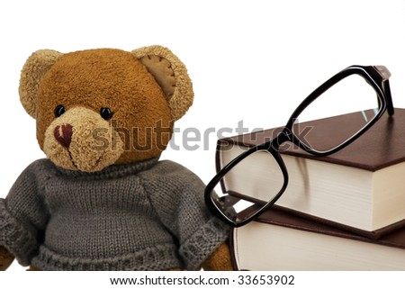 Teddy bear, glasses and a pile of old books on a white background - stock photo