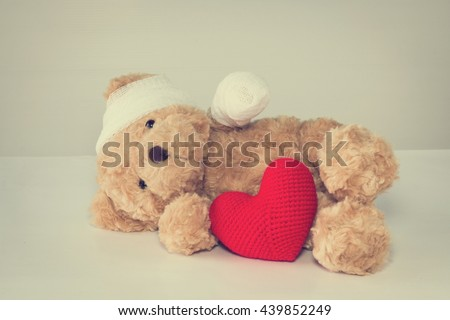 Teddy bear have an accident bandaged head and arm sleep on bed sick. with red heart yarn front side. copy space vintage style. - stock photo