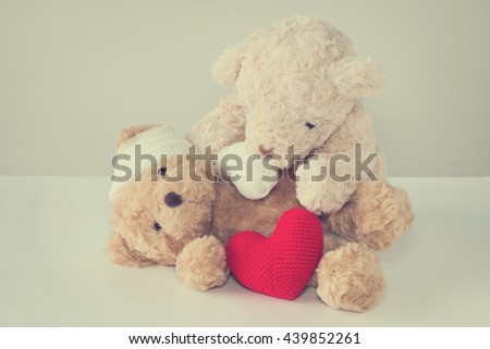 Teddy bear have an accident bandaged head and arm with one teddy bear hugging take care. red heart yarn front side. copy space vintage style. - stock photo