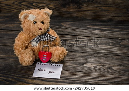 Teddy Bear, heart lock on old wood background.Valentines Day background.