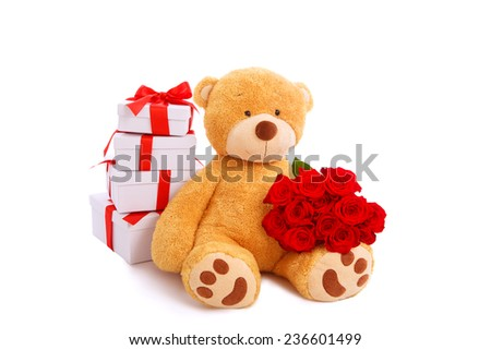Teddy bear holding bouquet of red roses with stack of gift boxes at background, valentines day. Studio shot, over white background with copy space.