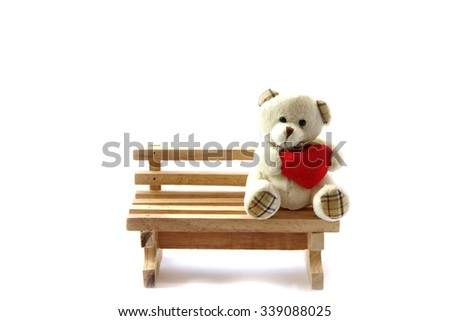 Teddy bear holding Red Heart on brown chair for you inscription. Isolated on white background - stock photo