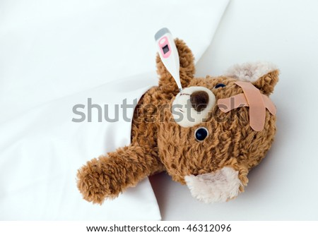 Teddy bear ill in bed - stock photo