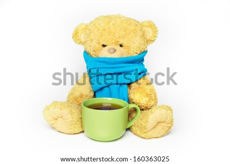 Teddy bear in a blue scarf with a big green mug of tea. The bear looks sick and sad. Isolated on white. - stock photo