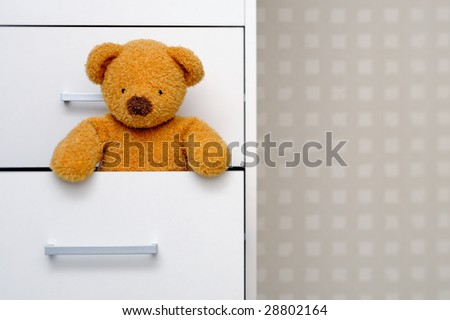 Teddy bear in dresser - stock photo