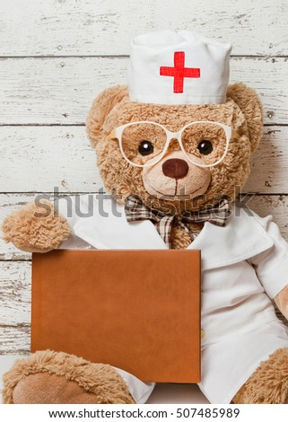 Teddy bear in medical clothing with the book