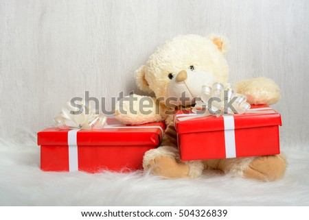 Teddy bear in santa hat with presents sitting on a white carpet
