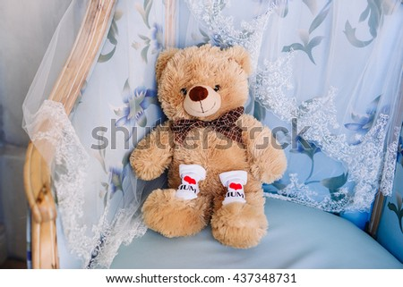 """Teddy bear on chair booties with a funny inscription """"I love mom"""" - stock photo"""