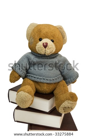 Teddy bear on pile of old books - stock photo