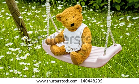 Teddy bear on swing - stock photo