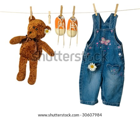 Teddy bear on washing line with sneakers and dungarees - stock photo