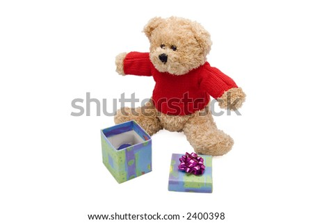 teddy bear opening a gift - stock photo