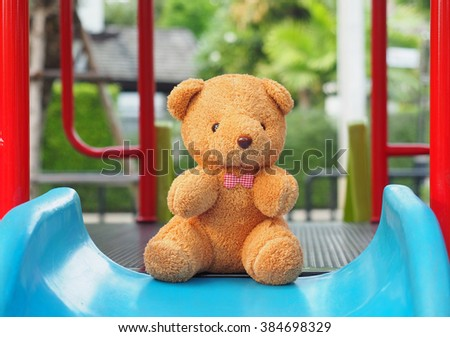 Teddy bear sitting alone on slide plastic colorful playground for children - stock photo