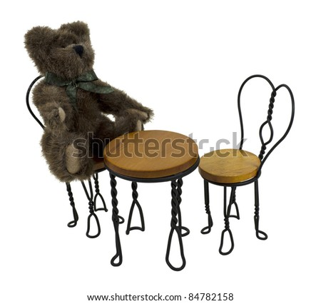 Teddy bear sitting at a Bistro setting with a table and a set of chairs for easy dining - path included - stock photo