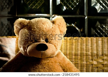 Teddy bear sitting by a wood stove - stock photo