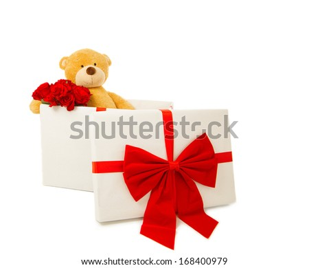 Teddy bear sitting in a gift box with red bow and holding bouquet of red roses. Studio shot, isolated, over white background with copy space.