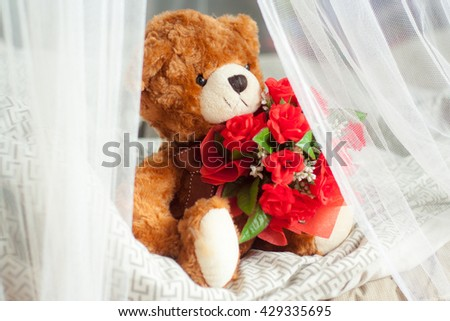 Teddy Bear sitting on bed and holding bunch of red roses around by mosquito net. / Teddy bear - stock photo