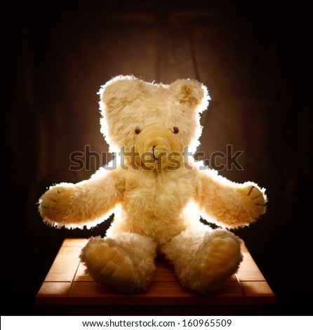 Teddy bear sitting on table with dark background. - stock photo