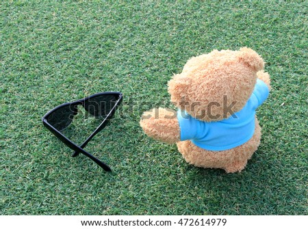 Teddy bear sitting on the green grass with sunglasses . Concept about travel