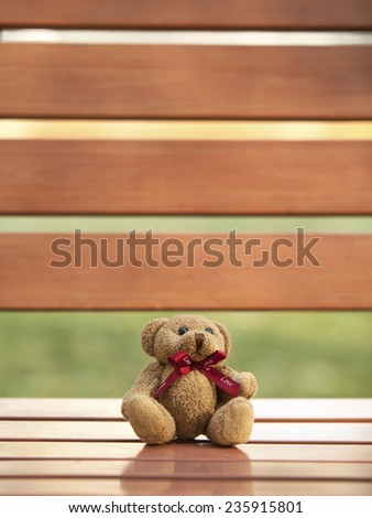 Teddy Bear sitting on the wooden chair  - stock photo