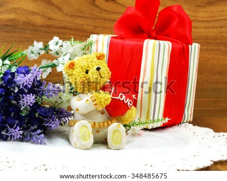 teddy bear sitting with a red heart and christmas gift boxes wrapped with paper - stock photo